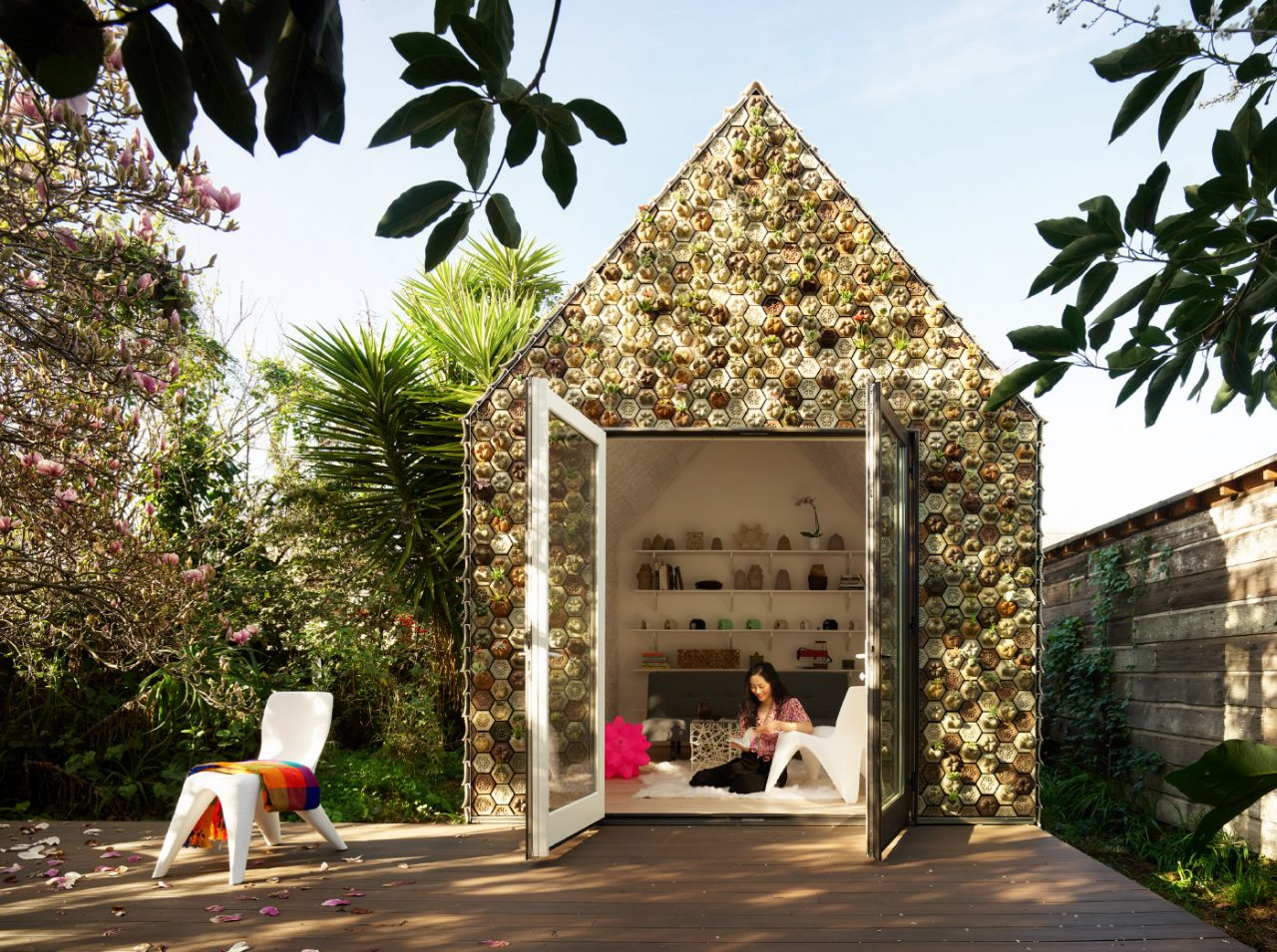 A gabled cabin covered in 3D printed plant pots