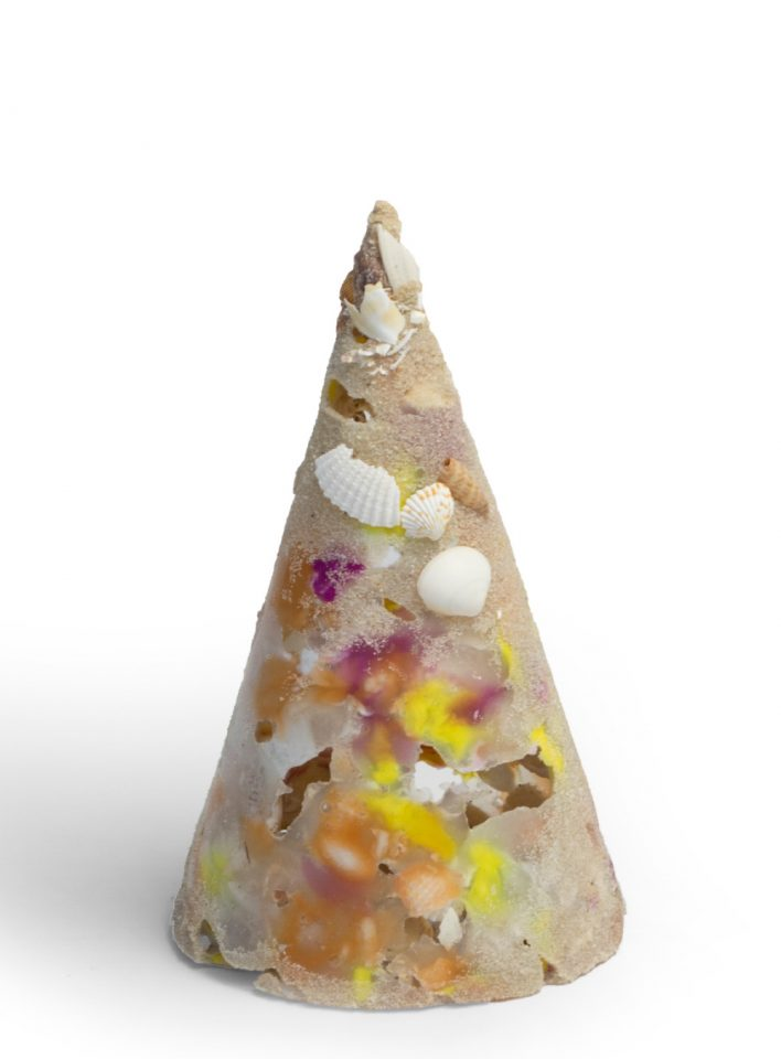 A cone comprised of sand, plastic, and shells