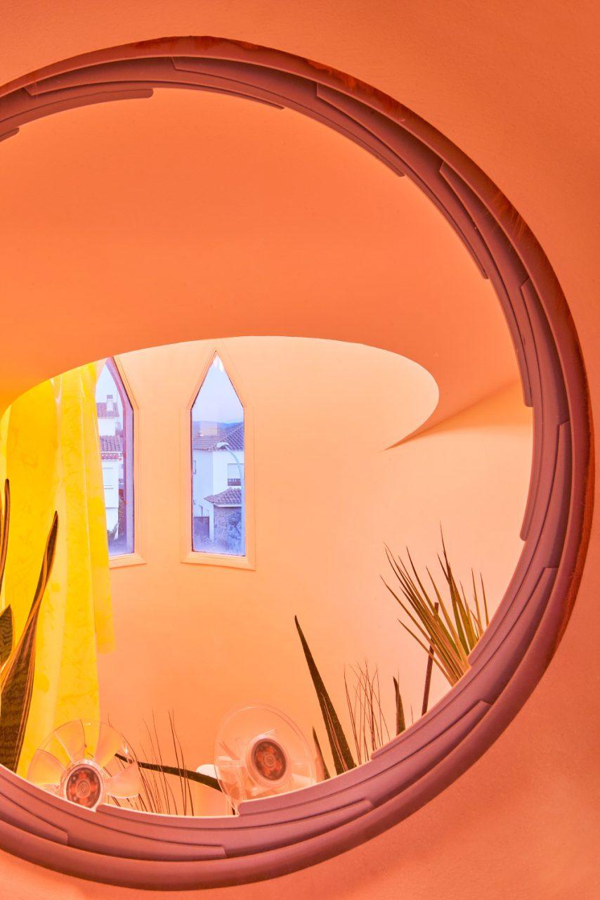 Porthole view into an orange staircase