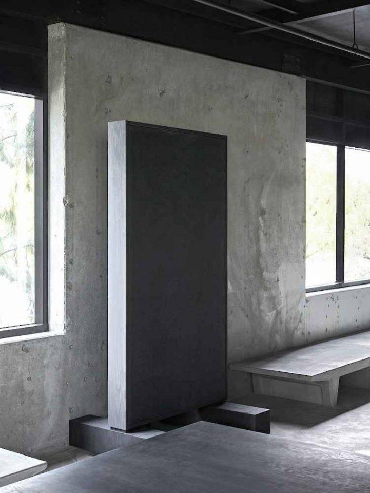 An upright black slab against concrete