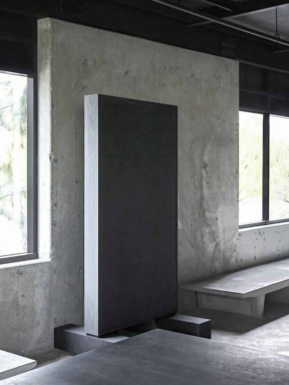 An upright black slab against concrete