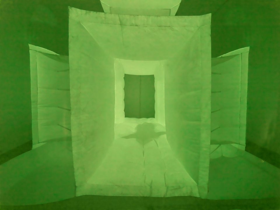 A green fabric with the shadow of a person moving through it