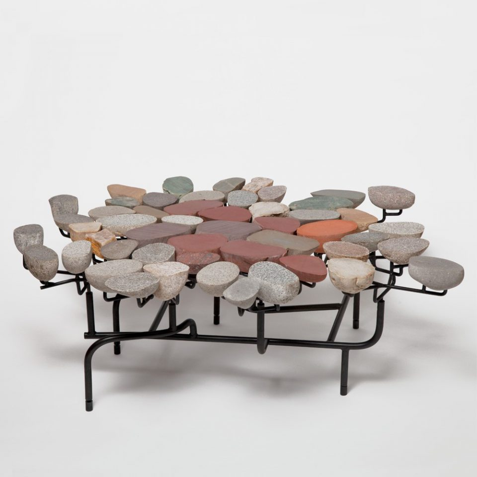 A table comprised of pebbles and black steel