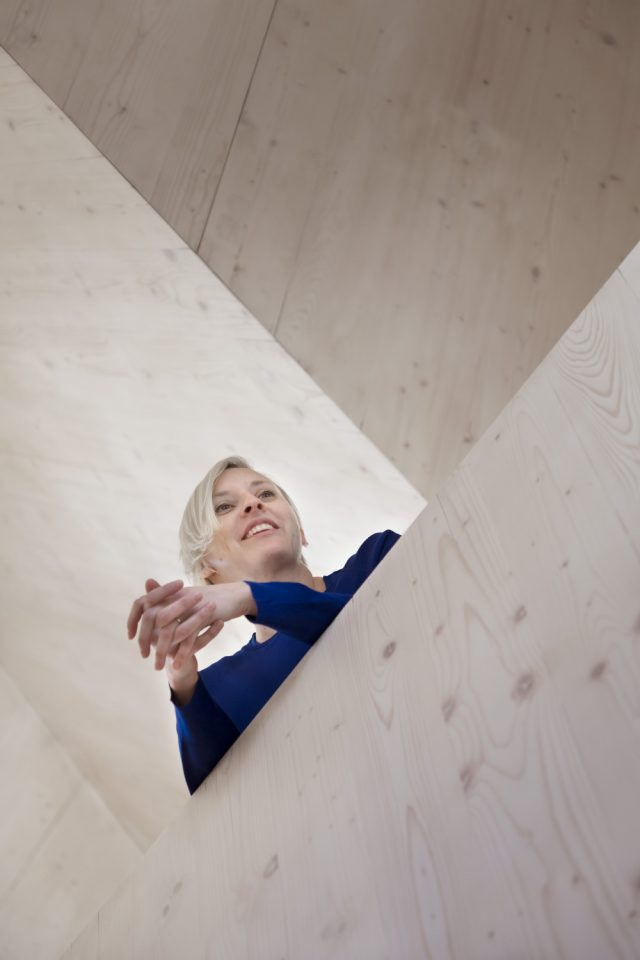 A woman leaning over timber construction
