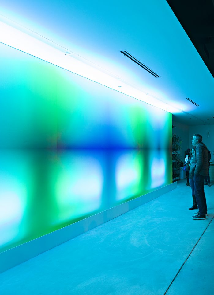 two people standing in front of a light installation
