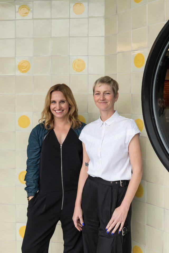 Two women against tile