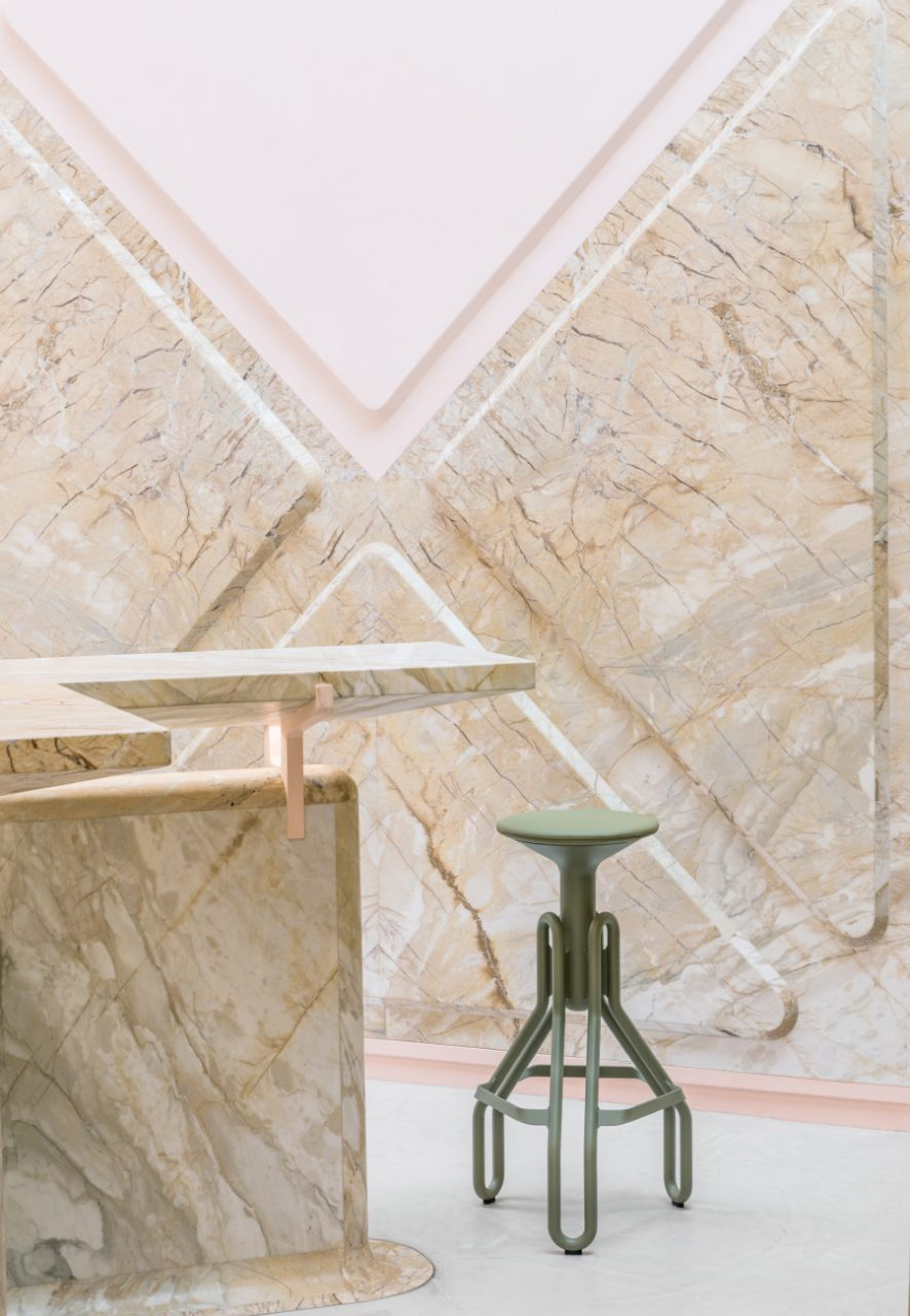 Close up view of a marble wall and green stool