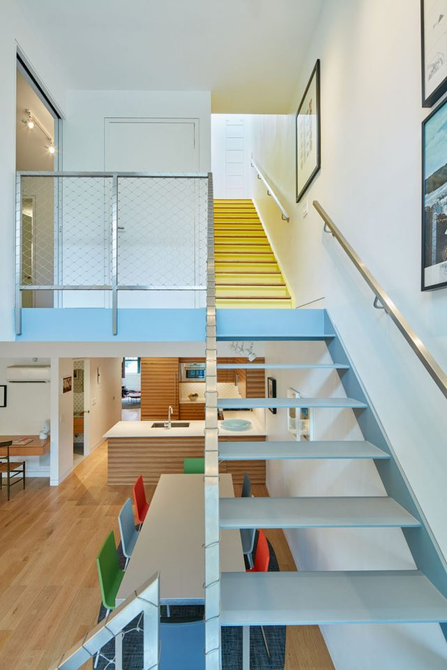 photo of a staircase in an apartment with a dinning room and kitchen in foreground