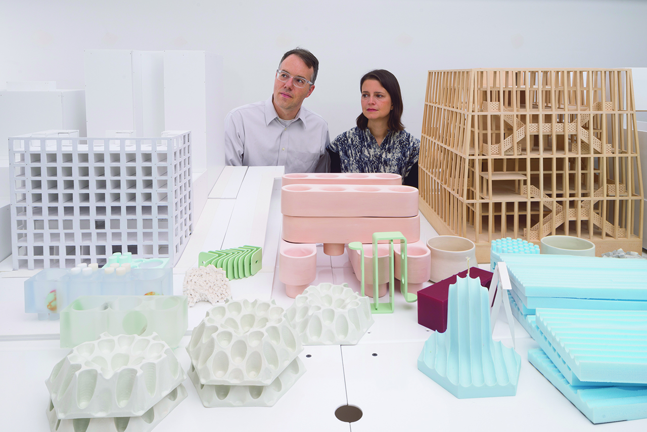 photo of a man and women behind a series of architectural models