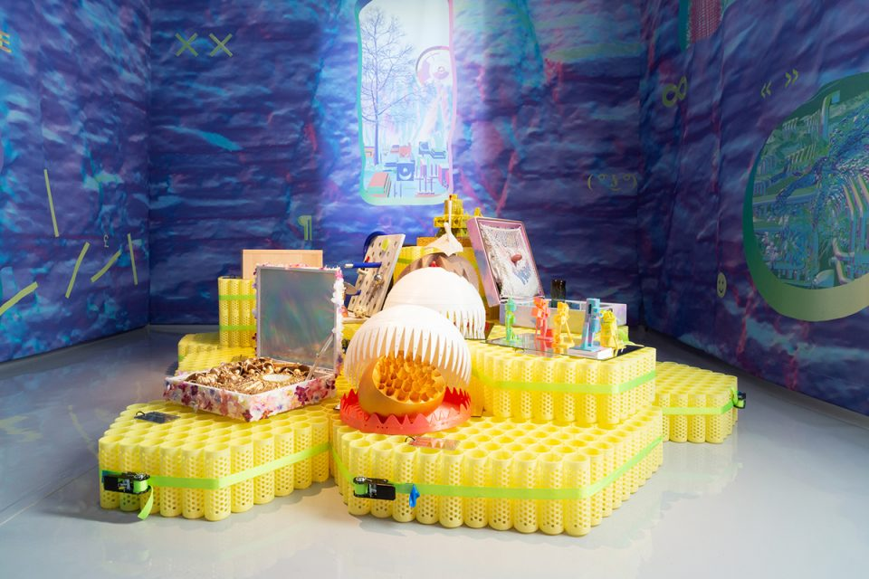 Photo of yellow plastic pedestals supporting small plastic objects in a room with blue-purple walls
