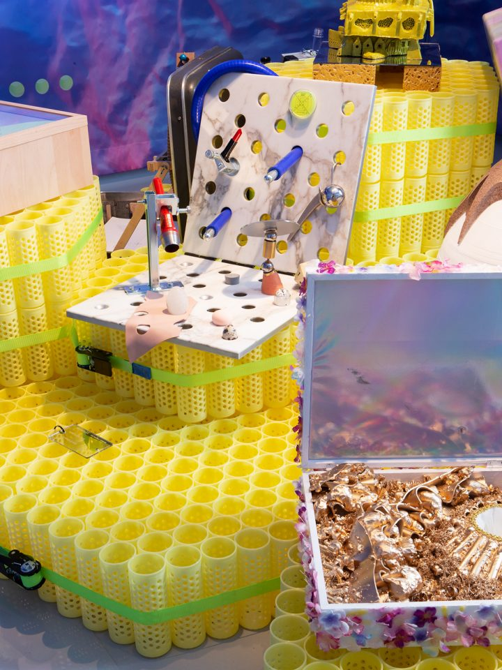 Photo of yellow plastic pedestals supporting displays with many little objects