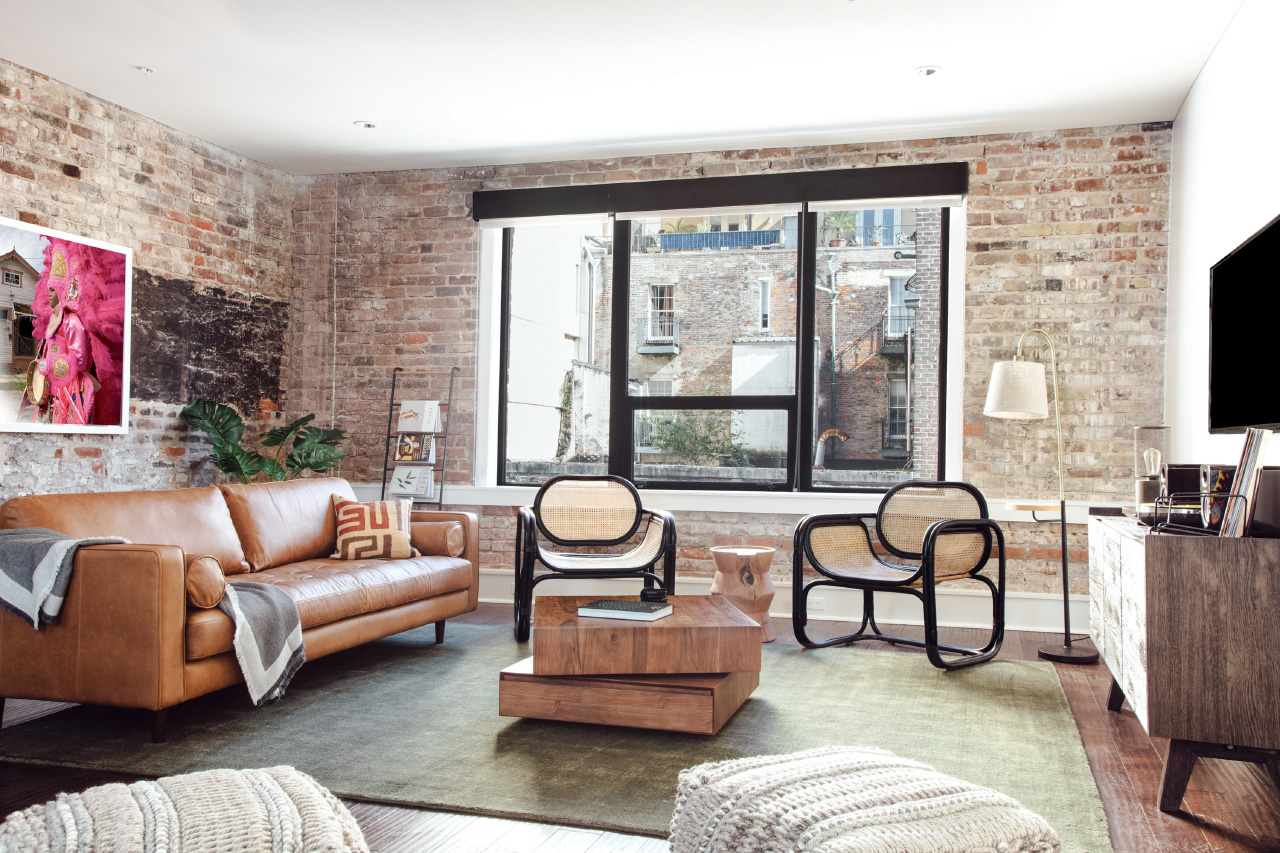 A living room with brick walls and rattan chairs