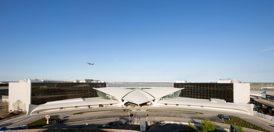 Photo of TWA Flight Center exterior with two glass and concrete rectangular hotel structures behind it