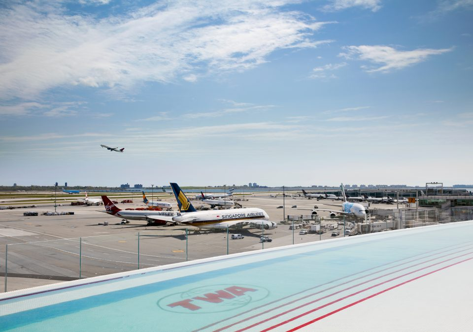 Photo of infinity pool that overlooks airplanes on tarmac at JFK