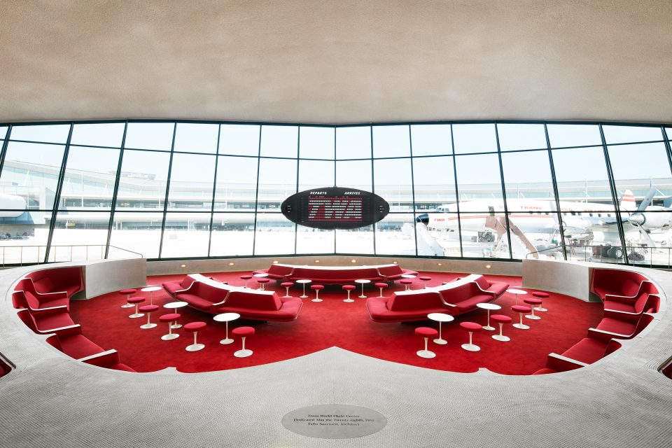 Interior image of red carpeted seating area that overlooks exterior tarmac at JFK