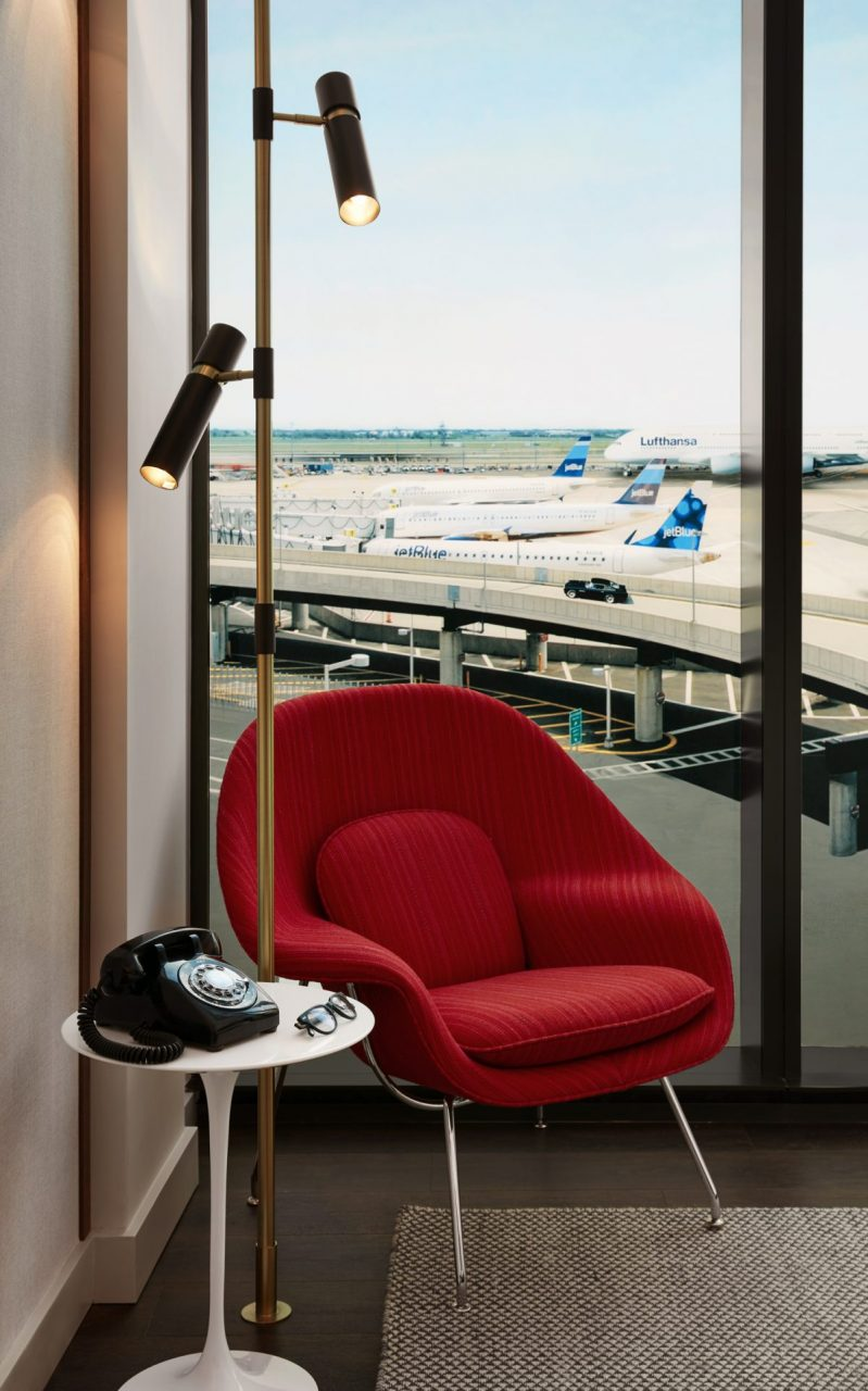 Interior image of butterfly chair, Saarinen table, old telephone in hotel room