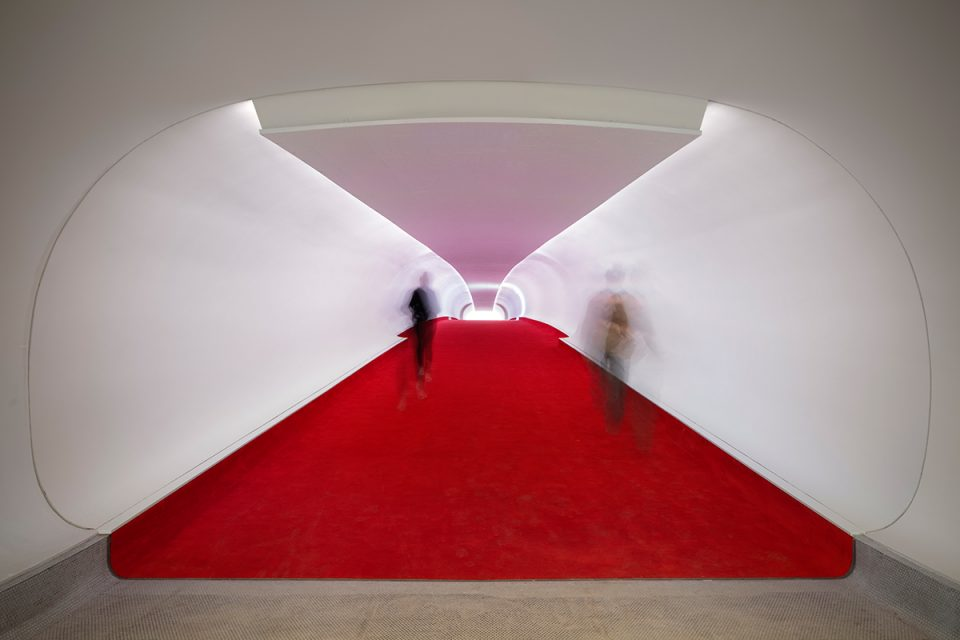 Image of red-carpet lined white tubes and blurred people walking through