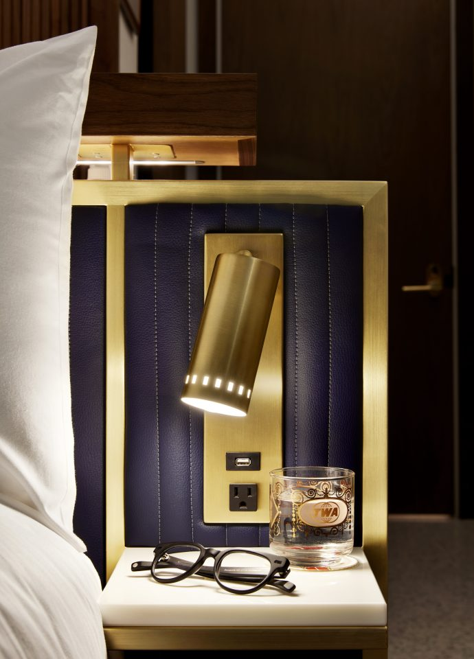 Up close image of brass light fixture and TWA branded glass
