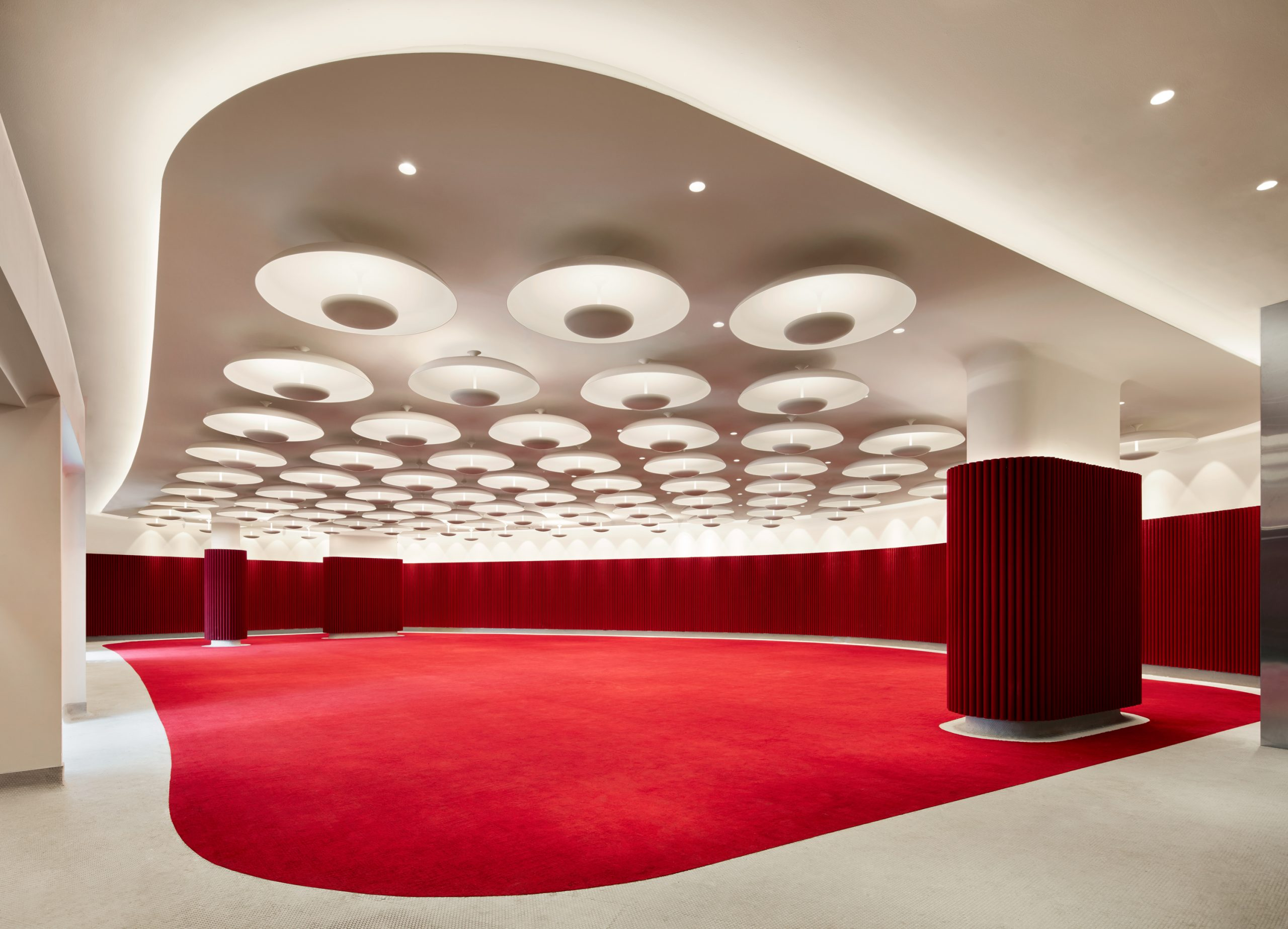 Interior image of ballroom with red carpet and walls and white ceiling with round lights