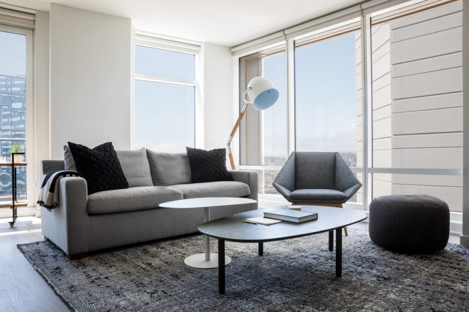 A living room with large windows and a white lamp