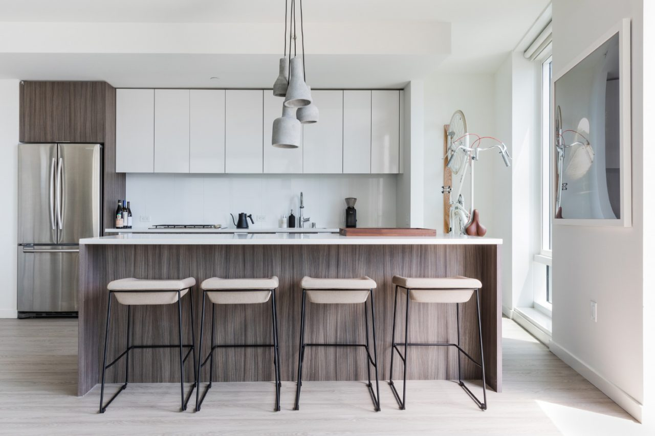 A kitchen with dining area and dangling concrete lights.