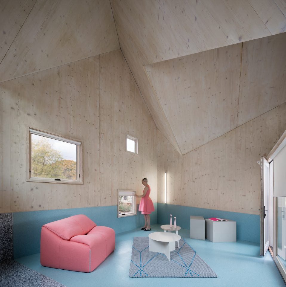 Image of Haus Gables living room with blue floor and pink furniture