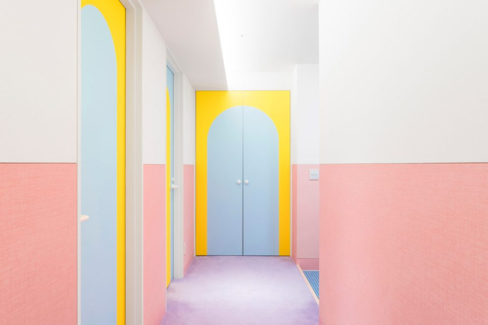 A pink hallway with yellow doors