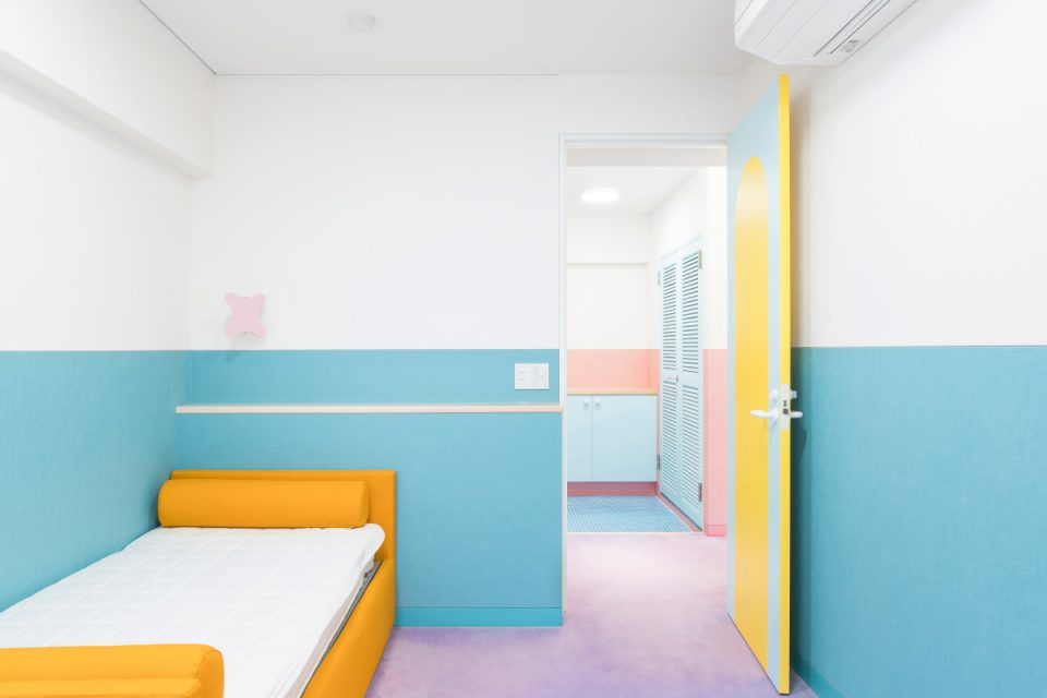 A bedroom with orange bed and blue walls