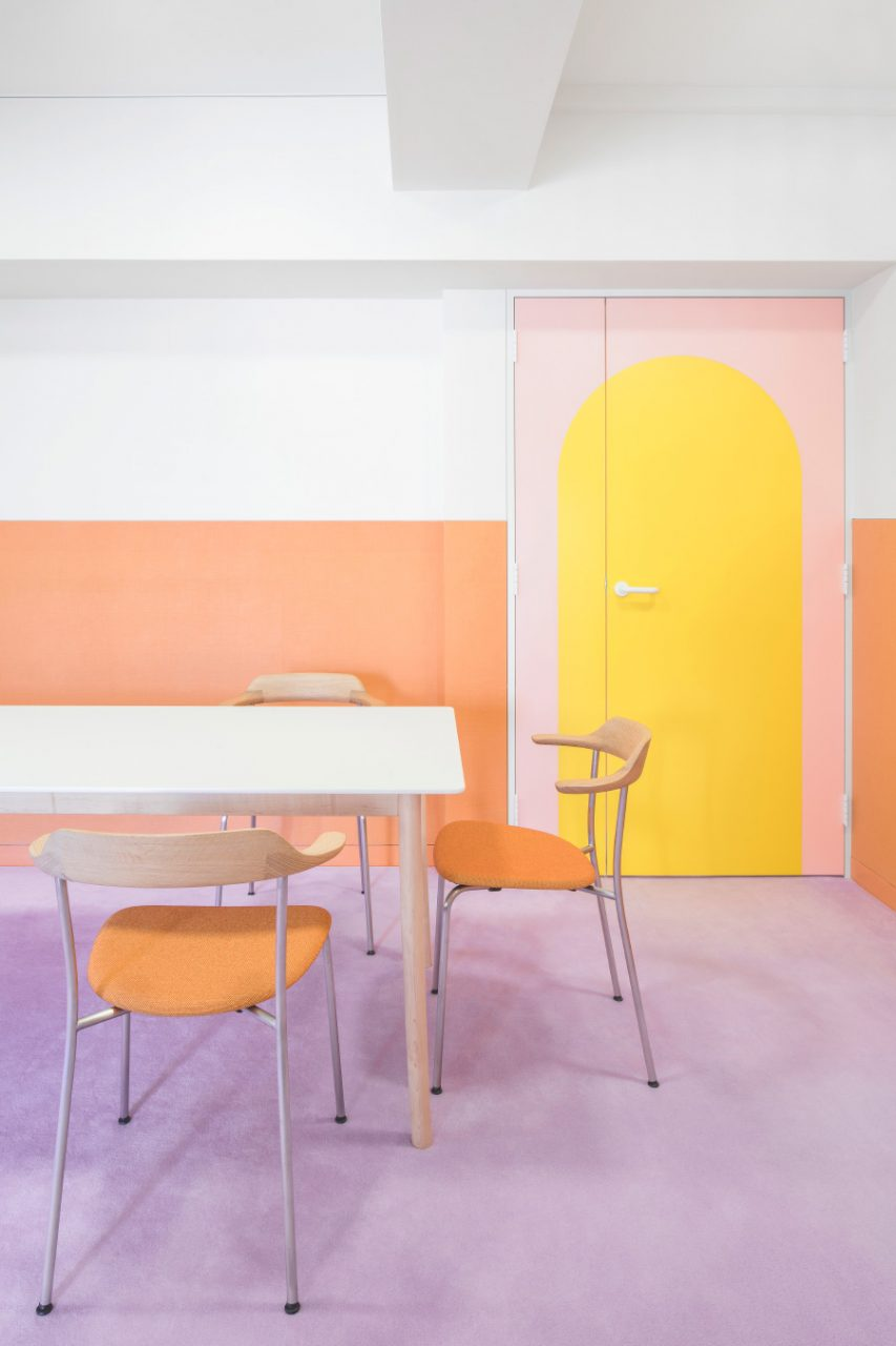 A dining room with pink carpeting and wooden chairs