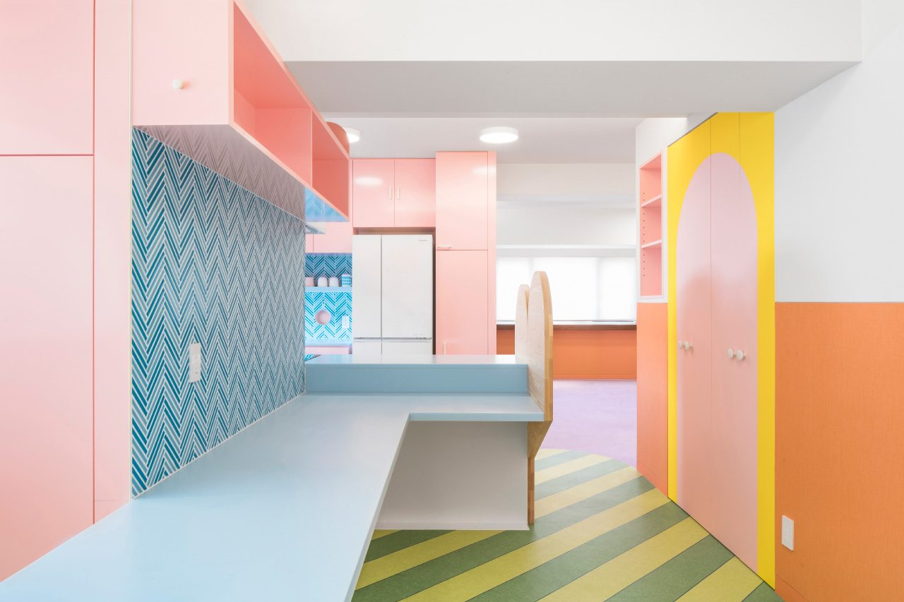 A pastel pink kitchen with blue tile backsplash and green striped floors