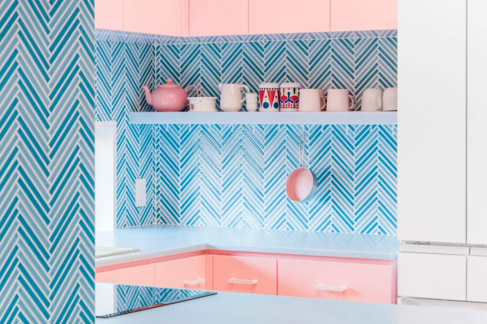A pink kitchen with a blue backsplash