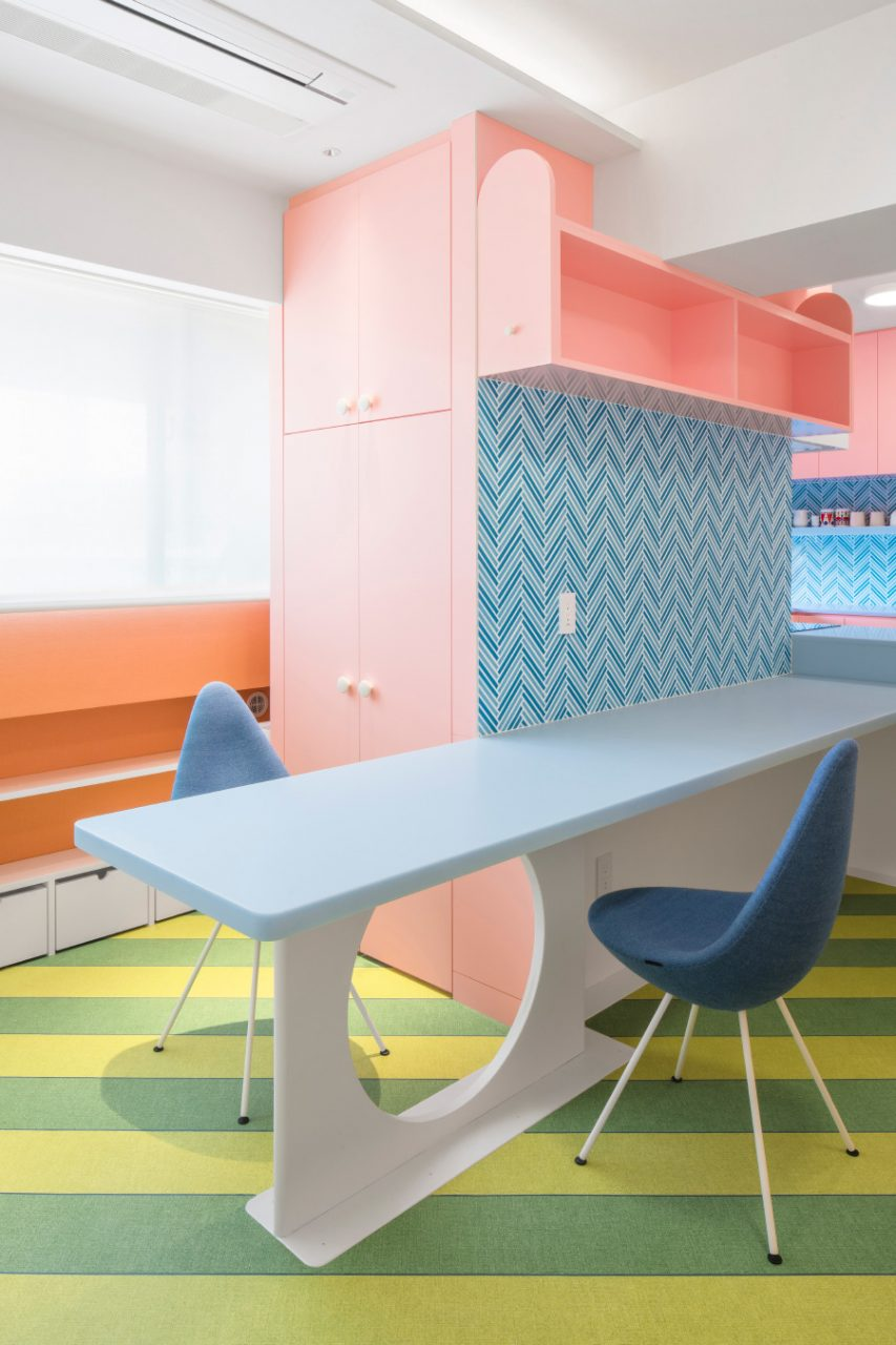 A blue countertop emerging from a pink kitchen, with two chairs
