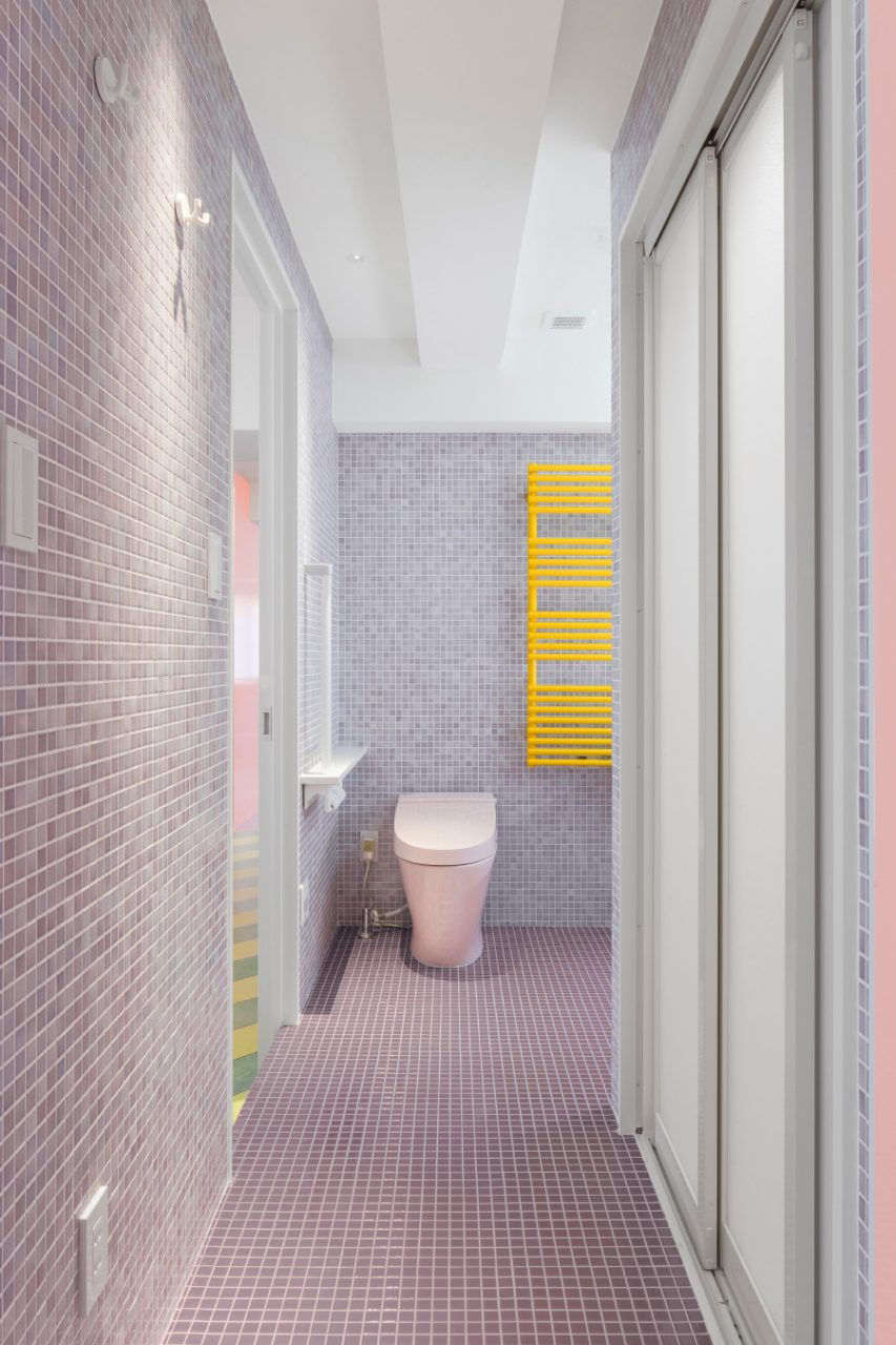 A tile-clad bathroom with a pink toilet