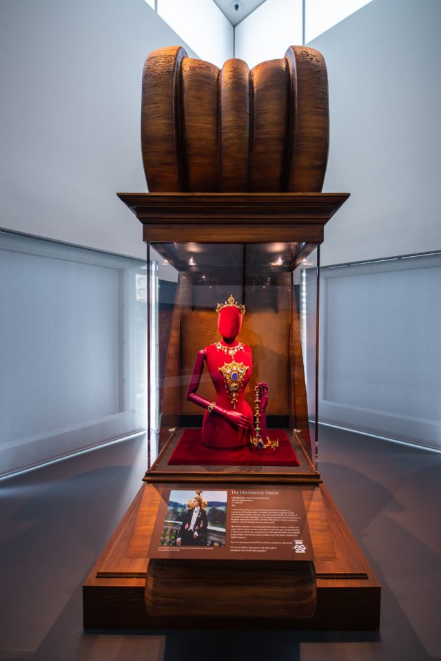 A red figure wearing jewels atop a wood stand