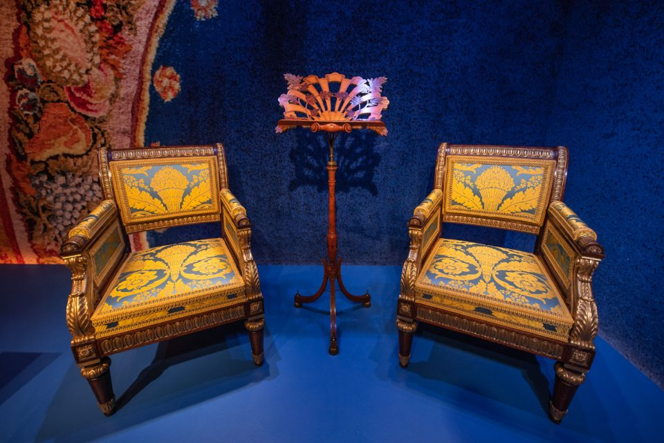 A set of yellow and blue armchairs against blue fabric