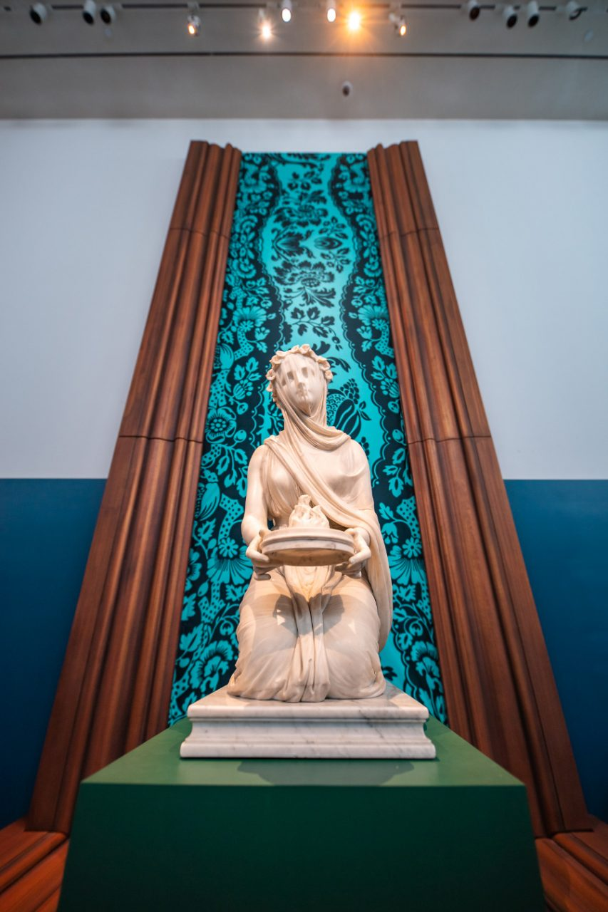 A marble woman atop a plinth with a bright green background