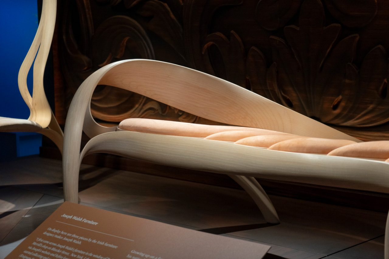 A wooden bench with a curved, flared arm