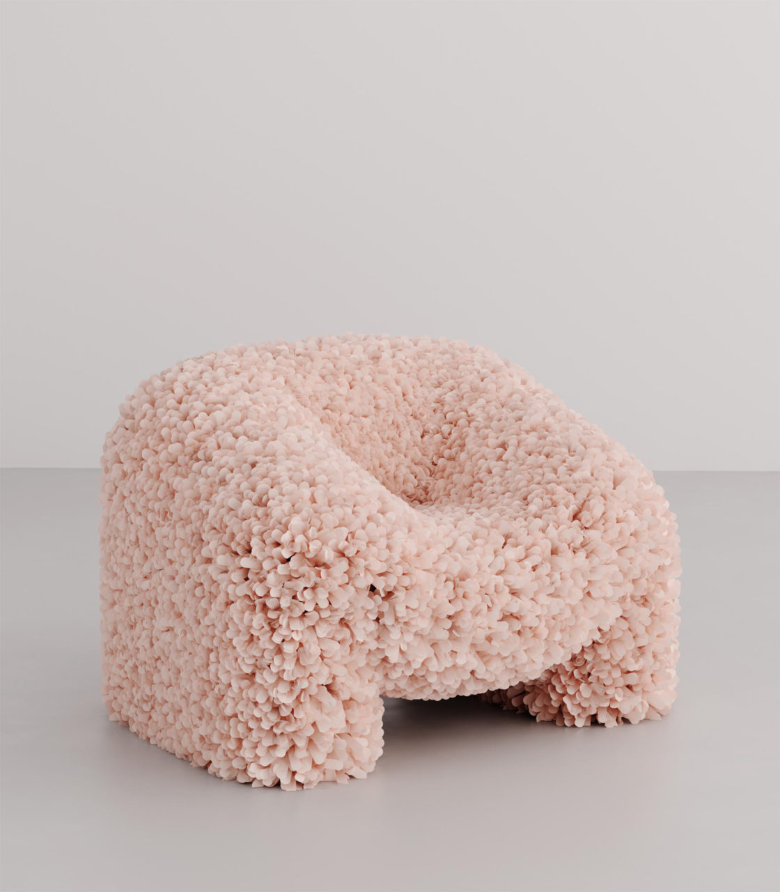 a pink, organic-shaped armchair upholstered in a loose weave textile