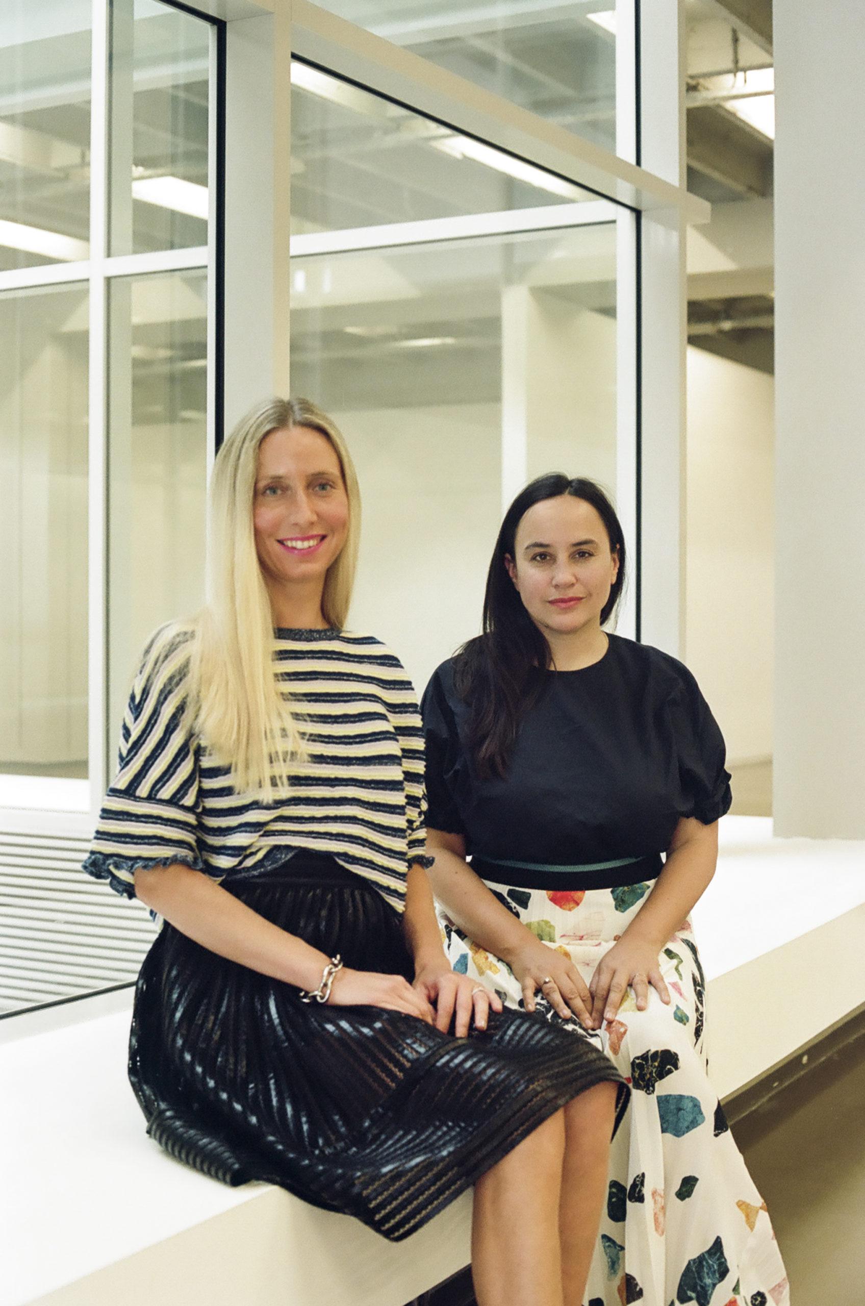 portrait of two women sitting from aa window in a gallery space