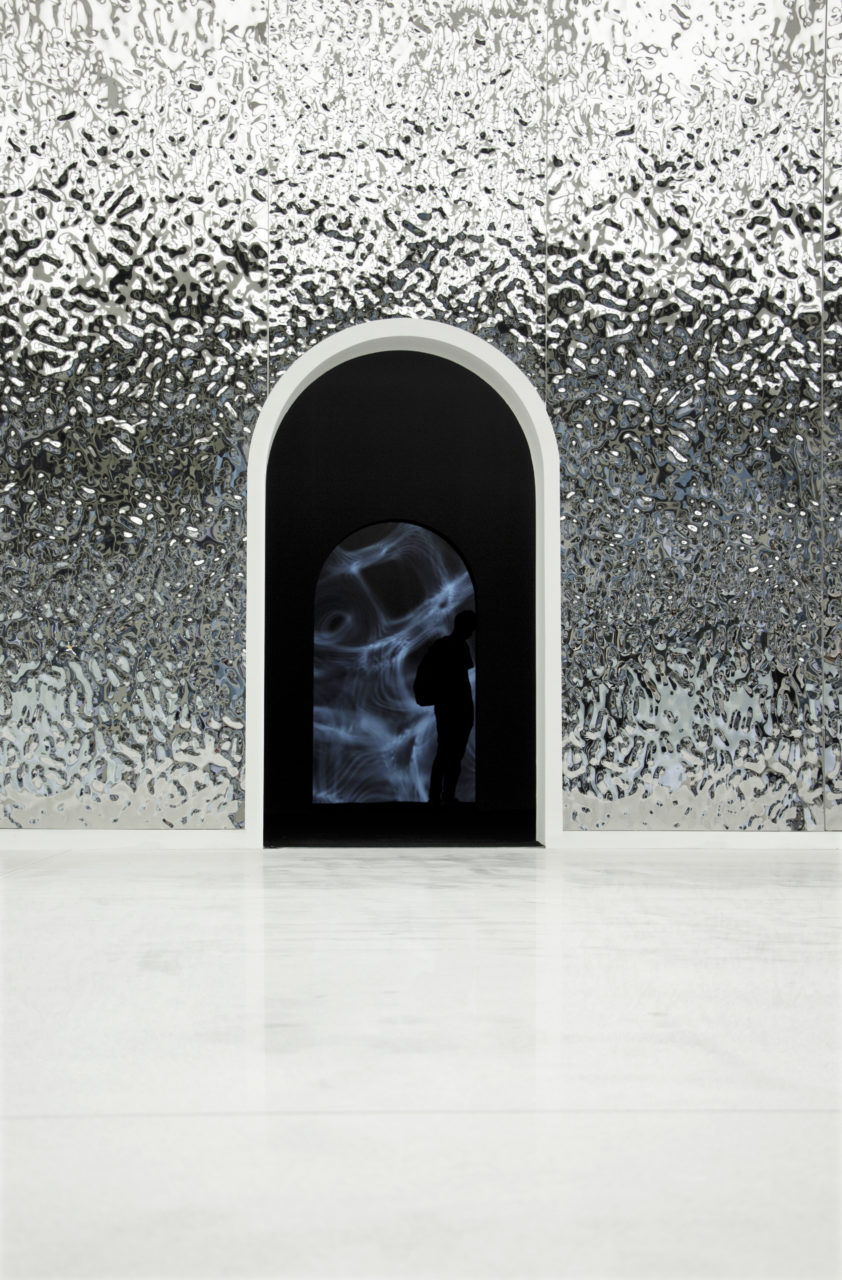 A rendering of an archway cut into a textured and reflective metallic surface. the silhouette of a figure can be found with in the archway