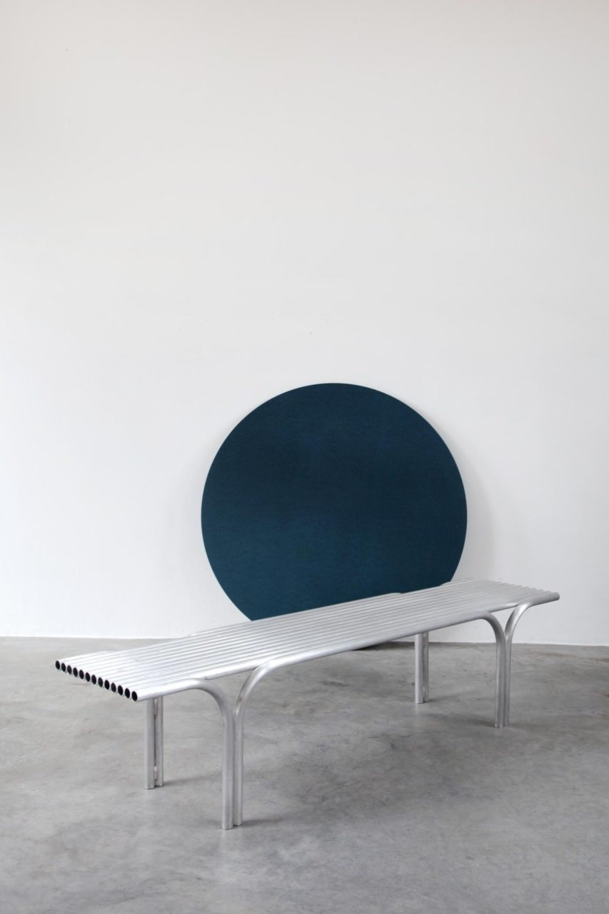 Image of a bench made of metal tubes in front of a blue circle carpet mounted on a white wall