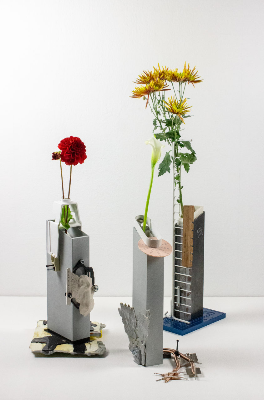 A series of angular vases holding different type of flowers in front of a white backdrop