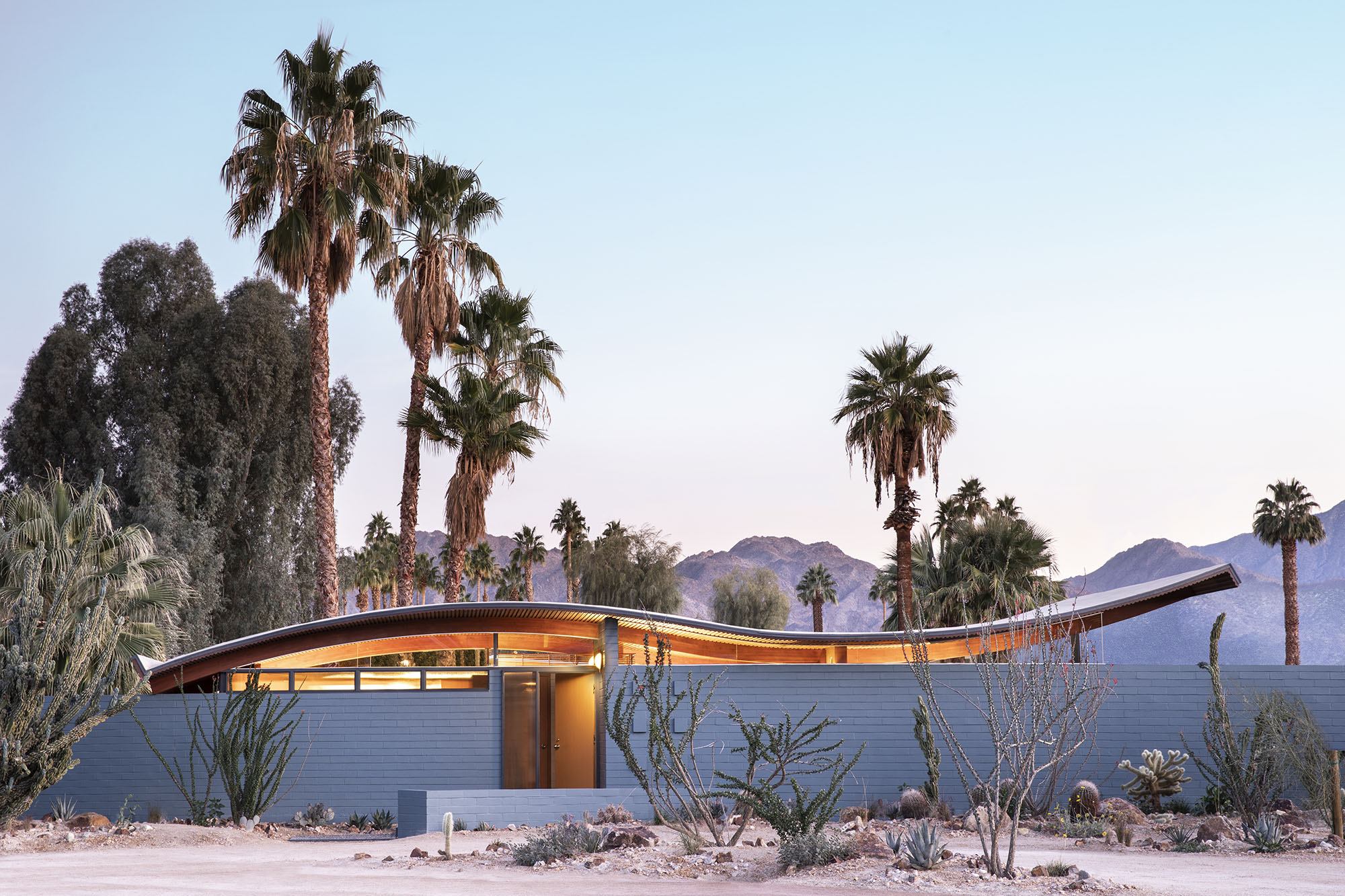 exterior view of a single story home with wave-shaped roof set in a desert landscape with palm trees
